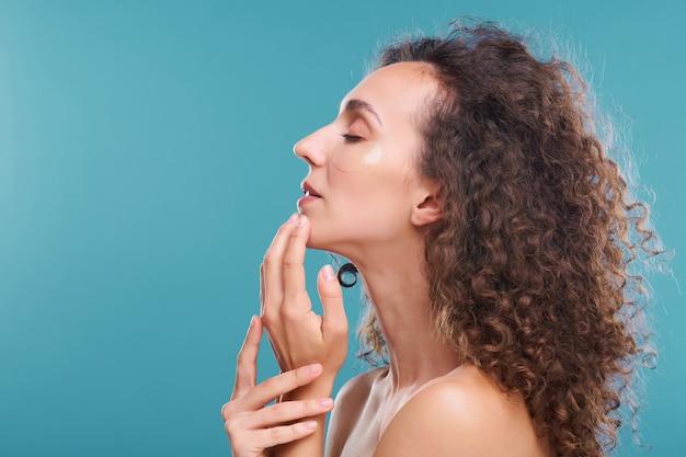 Profil de la belle jeune femme aux longs cheveux ondulés foncés bénéficiant d'une sensation de fraîcheur sur son visage au cours de la procédure de soin de la peau sous les yeux