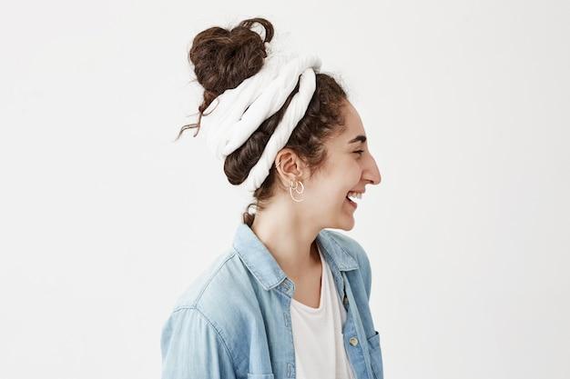 Profil de la belle jeune femme en do-rag et chemise en jean tendance, se détendre à l'intérieur, en détournant les yeux avec un joli sourire, posant contre un mur blanc avec un espace de copie pour le texte ou le contenu publicitaire