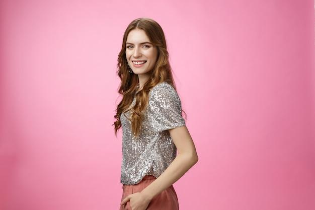 Profil confiant élégant glamour jeune femme coiffure frisée chemisier scintillant tournant caméra smili...