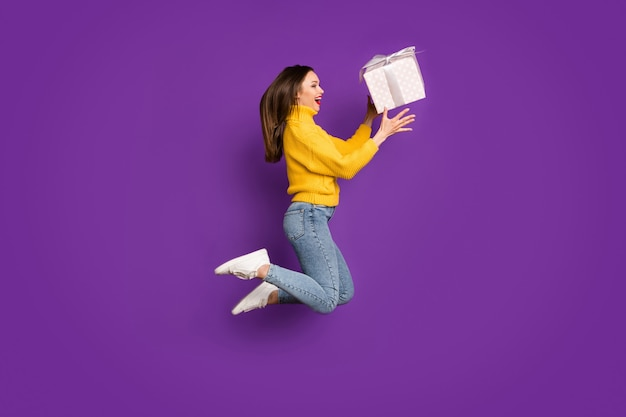 Profil de côté pleine longueur portrait de la taille du corps de joyeuse femme positive ravie attraper boîte-cadeau sautant vers le haut.