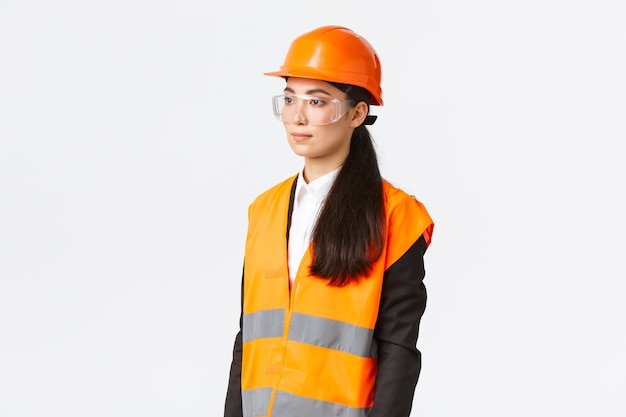 Profil de femme d'affaires asiatique grave inspectant la zone de construction