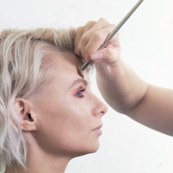 Profil de femme blonde close up avec une main d'une femme maquilleuse traitant son front ou ses sourcils