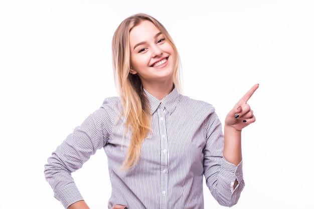 Profil d'une femme pointant et présentant à côté isolé sur un mur blanc