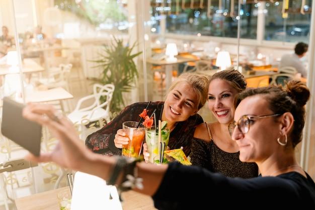 Profil de femmes faisant un selfie assis sur une terrasse en train de boire des cocktails la nuit