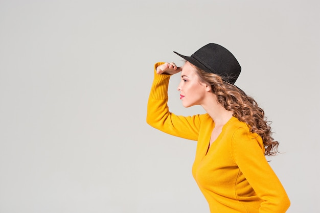 Le profil de la fille émotive au chapeau sur le mur gris