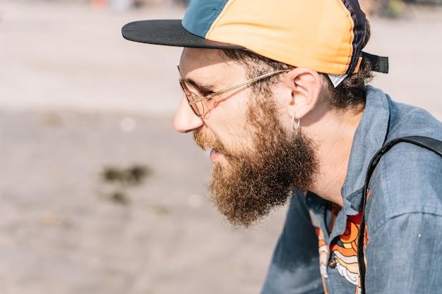 Profil d'un garçon rousse avec une barbe et une casquette portant une chemise en jean imprimée