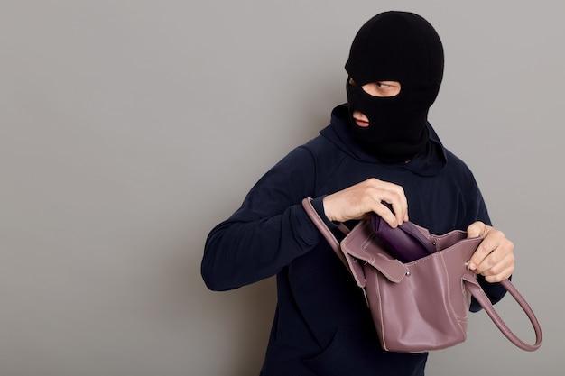 Profil d'un gars voleur avec un visage masqué