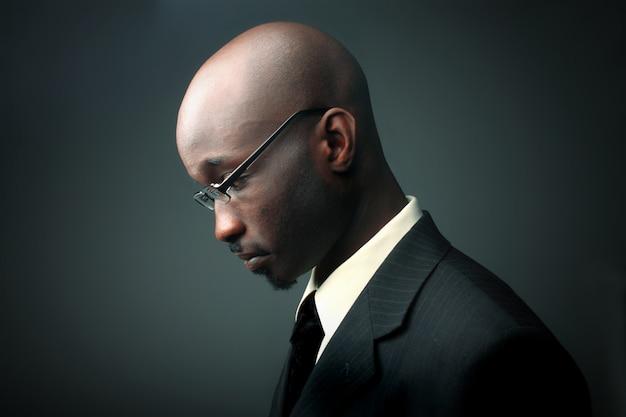 Profil d'un homme d'affaires africain avec une expression triste