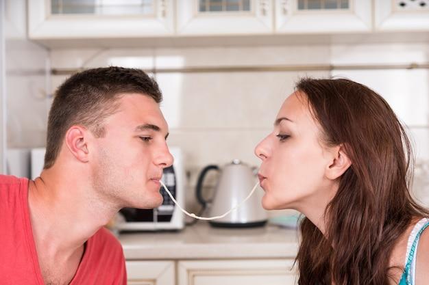 Profil de jeune couple romantique à l'heure du dîner partageant un seul brin de spaghetti, sirotant ensemble jusqu'à ce qu'ils s'embrassent