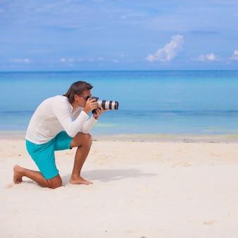 Profil de jeune homme avec une caméra à la main sur la magnifique plage de sable blanc