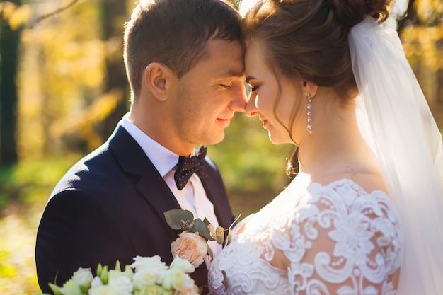 Profil des jeunes mariés aux yeux fermés dans le parc se bouchent
