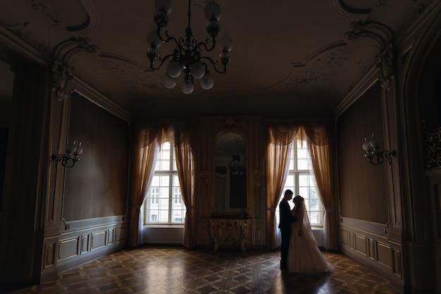 Profil de jeunes mariés s'embrassant dans un hall avec de beaux intérieurs et de grandes fenêtres