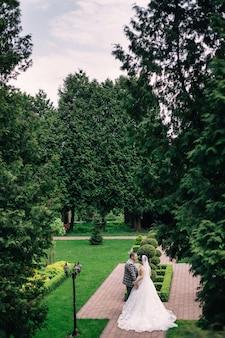 Profil des jeunes mariés se tiennent la main et marchent dans un magnifique parc. belle robe de mariée avec robe longue queue.