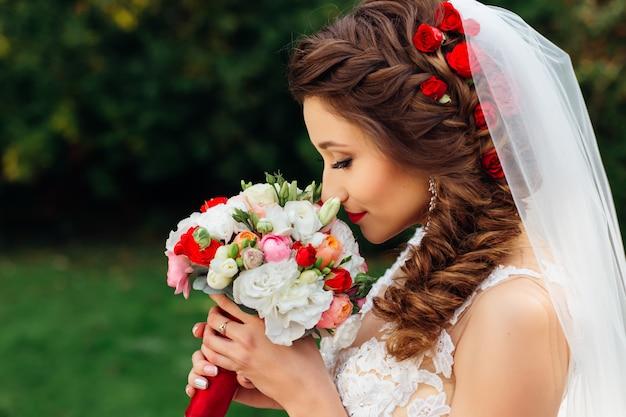 Profil de mariée avec une coiffure chic tient le bouquet de mariage