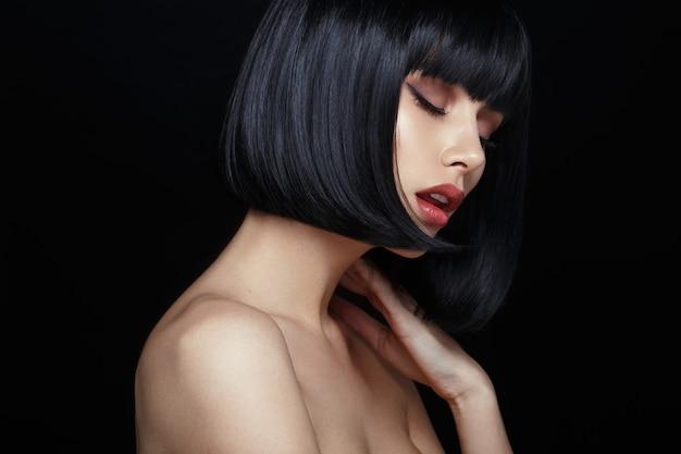 Profil d'un modèle sensuel en perruque noire, les yeux fermés, touche son cou, les épaules nues, isolé sur fond noir.
