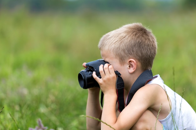 Profil portrait en gros plan du jeune garçon d'enfant beau et blond avec l'appareil photo prenant des photos à l'extérieur sur le printemps ensoleillé lumineux.
