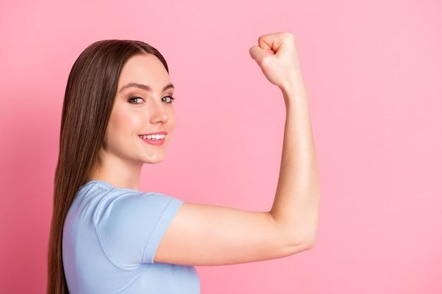 Profil de portrait photo de femme confiante montrant des biceps isolés sur fond de couleur rose pastel