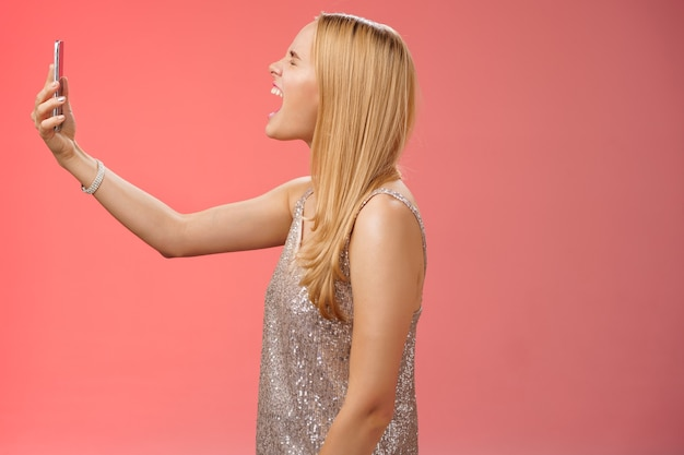 Profil tourné drôle femme blonde insouciante tenir le smartphone soulevé la bouche ouverte en criant enregistrement vidéo propre cri crier, debout robe glamour argentée près de fond rouge s'amuser.