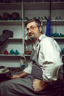 Profitant du processus de création de chaussures sur mesure. lieu de travail du créateur de chaussures. mains de cordonnier avec outil de cordonnier