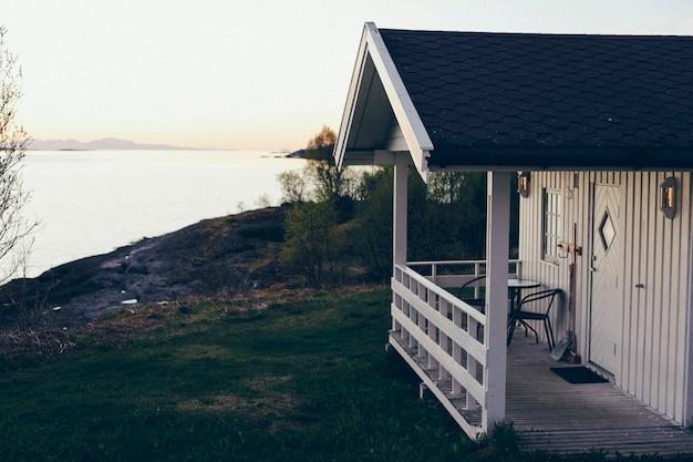 Profitant du soleil de minuit sur le porche d'un bungalow en bois norvégien, ajoutez du grain de film.