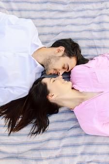 Profitant de la vue de dessus de la proximité de la belle jeune couple d'amoureux couchés ensemble.
