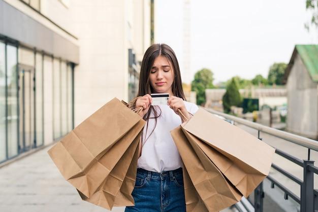 Profiter des achats de jour. sur toute la longueur de la jeune femme tenant des sacs à provisions et souriant en marchant le long de la rue