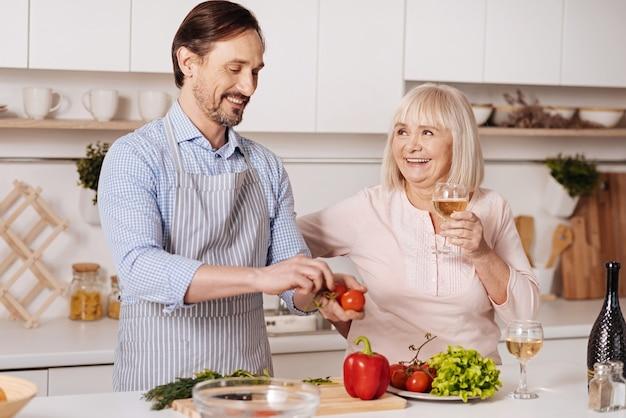 Profiter d'une alimentation saine. heureux homme mûr vivant debout dans la cuisine et la cuisson de la salade végétarienne tandis que sa mère senior buvant du vin