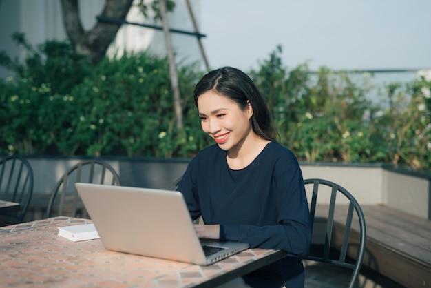 Profiter des avantages du wi-fi gratuit. belle jeune femme travaillant sur ordinateur portable et souriante assise à l'extérieur