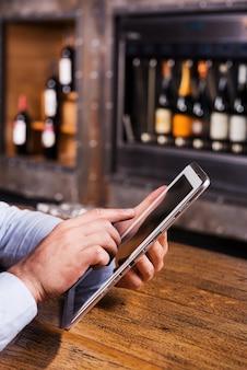 Profiter des avantages du wi-fi gratuit. gros plan d'un homme en chemise bleue travaillant sur une tablette numérique alors qu'il était assis au comptoir du bar