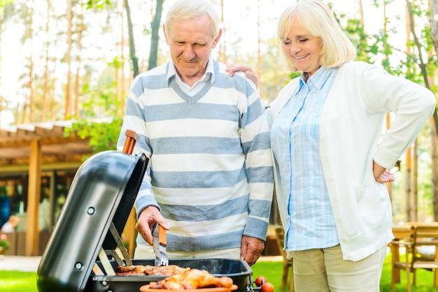 Profiter d'un barbecue ensemble. joyeux couple de personnes âgées faisant griller de la viande sur le gril tout en se tenant dans la cour arrière de leur maison