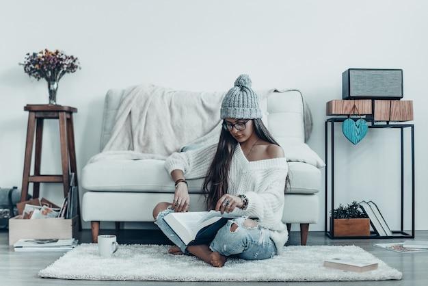 Profiter d'un bon livre. jolie jeune femme en tenue décontractée et livre de lecture de chapeau en tricot