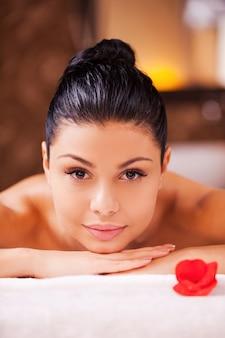 Profiter de la détente. vue de face de la belle jeune femme torse nu allongée sur la table de massage et regardant la caméra