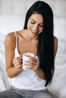 Profiter du café du matin. jolie jeune femme tenant une tasse et souriant