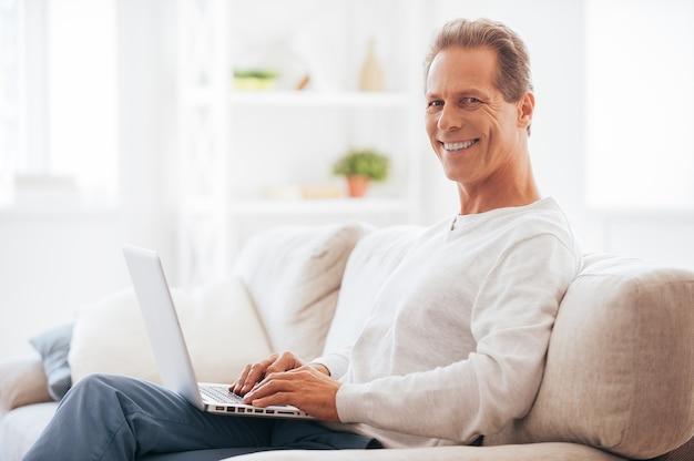 Profiter du temps libre à la maison. vue latérale d'un homme mûr travaillant sur un ordinateur portable et souriant assis sur le canapé à la maison