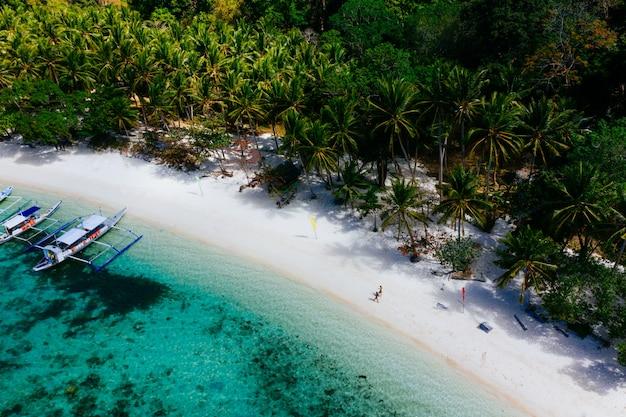 Profiter du temps à la plage. les gens qui marchent sur le sable blanc, avec la jungle tropicale. concept sur les voyages et la nature