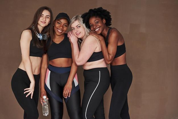 Profiter d'être ensemble. groupe de femmes multiethniques debout contre l'espace brun