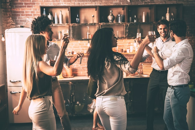 Profiter d'une fête à la maison avec des amis. jeunes joyeux dansant et buvant tout en profitant d'une fête à la maison dans la cuisine