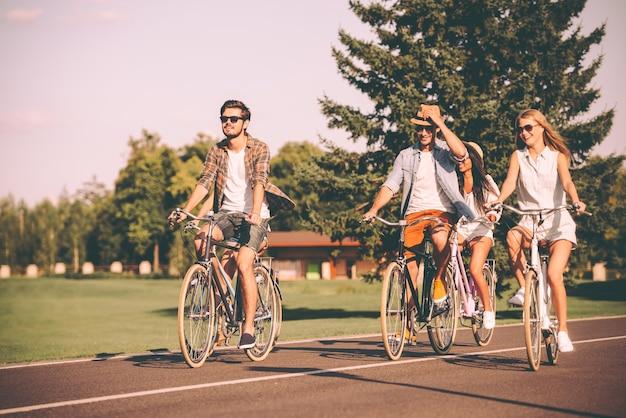 Profiter de la journée d'été ensemble. groupe de jeunes faisant du vélo le long d'une route et ayant l'air heureux