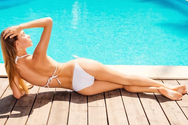 Profiter des journées d'été. vue arrière de la belle jeune femme en bikini blanc allongé près de la piscine et gardant les yeux fermés