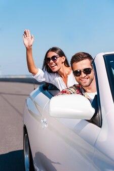 Profiter de leur road trip. heureux jeune couple profitant d'un voyage sur la route dans leur cabriolet blanc