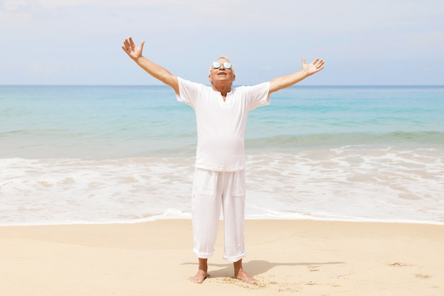 Profiter de la retraite. heureux homme senior marchant sur la plage.