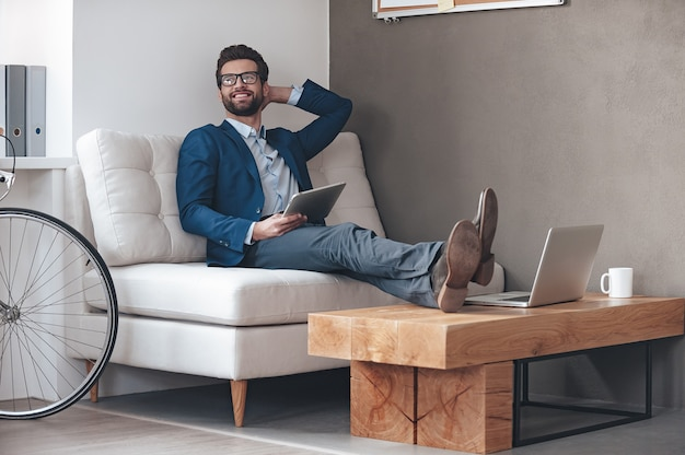 Profiter de sa journée de travail. beau jeune homme gai gardant les jambes sur la table et détournant les yeux avec le sourire alors qu'il était assis sur le canapé au bureau