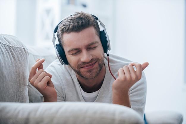 Profiter de sa musique préférée. jeune homme gai dans des écouteurs écoutant la musique et faisant des gestes