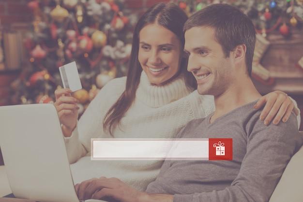 Profiter des soldes de noël. beau jeune couple achetant en ligne tout en utilisant un ordinateur avec un arbre de noël en arrière-plan