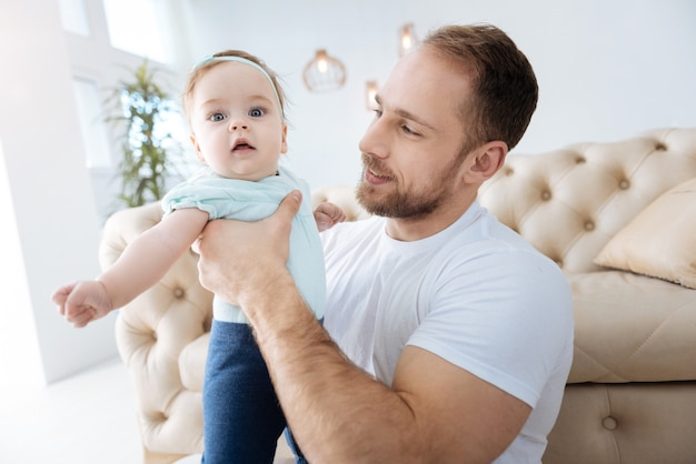 Profiter des traditions familiales. joyeux père barbu charismatique assis à la maison et tenant la petite fille dans ses bras tout en exprimant ses soins et son amour
