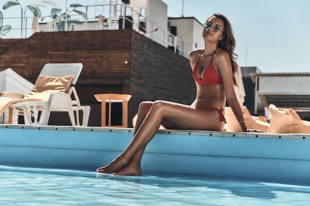 Profiter des vacances d'été. belle jeune femme en maillot de bain gardant les yeux fermés alors qu'elle était assise au bord de la piscine à l'extérieur