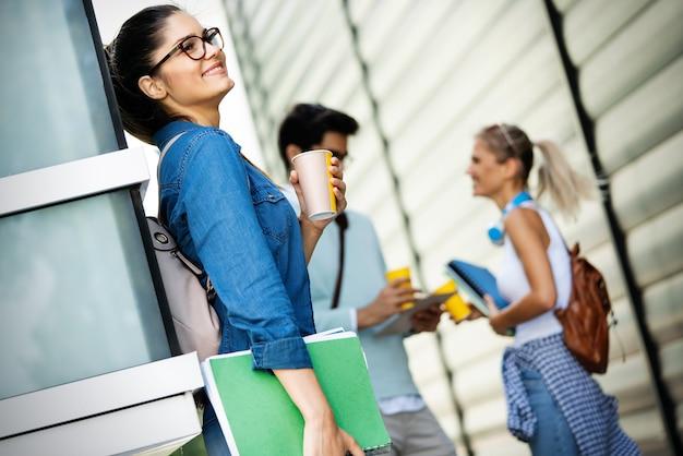 Profiter de la vie étudiante. jeunes étudiants souriants avec du café dans la rue de la ville. groupe d'amis ayant rompu ensemble.
