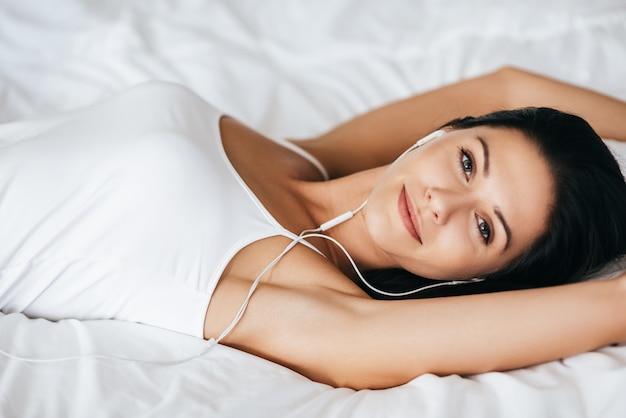 Profiter de votre musique préférée. vue de dessus de la magnifique jeune femme écoutant de la musique et regardant la caméra