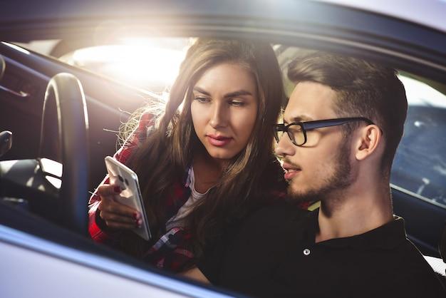 Profiter des voyages. beau jeune couple assis sur les sièges passagers avant et souriant tandis qu'un bel homme conduit une voiture et utilise un téléphone portable