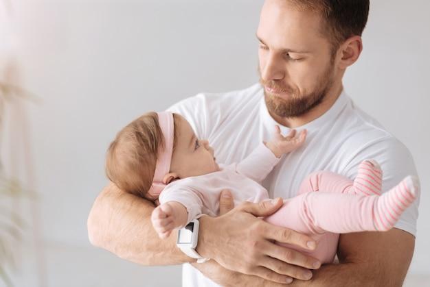 Profiter d'un week-end en famille. beau père heureux charismatique debout à la maison et tenant le nouveau-né dans ses bras tout en exprimant ses soins et son amour